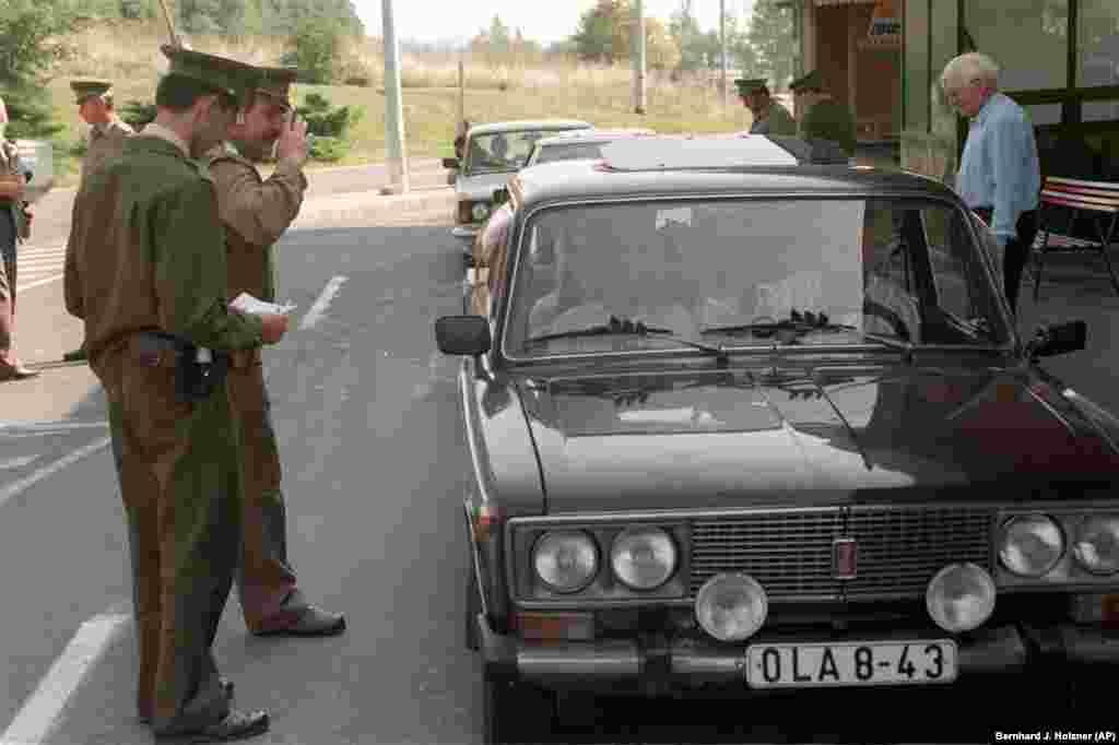 A Hungarian customs officer checks passports belonging to East Germans on September 11.