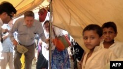 Richard Holbrooke, U.S. envoy for Afghanistan and Pakistan, enters a tent to meet a displaced family from the Swat and Buner district in Mardan, Pakistan, in June.