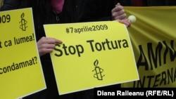 """Amnesty International"" guramasynyň Moldowada gynamalara garşy gurnan protest çäresinde göterilen käbir şygarlar. Kişinýew, aprel, 2009."