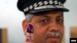 شرطي عراقي يظهر سبابته بعد الإدلاء بصوته