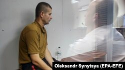 Volodymyr Petrovets sits inside the defendants cage at Holosiivskyi district court in Kyiv on June 4.