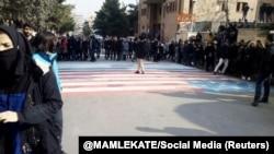 Students walk around, instead of across, U.S. and Israeli flags at the Shahid Beheshti University in Tehran on January 12.