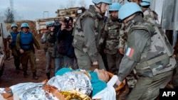 UN personnel carry away a victim of the Markale market attack in Sarajevo on February 6, 1994.