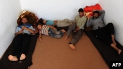 Afghan refugees sit at a UN refugee agency center in Herat after being deported from Iran in September.