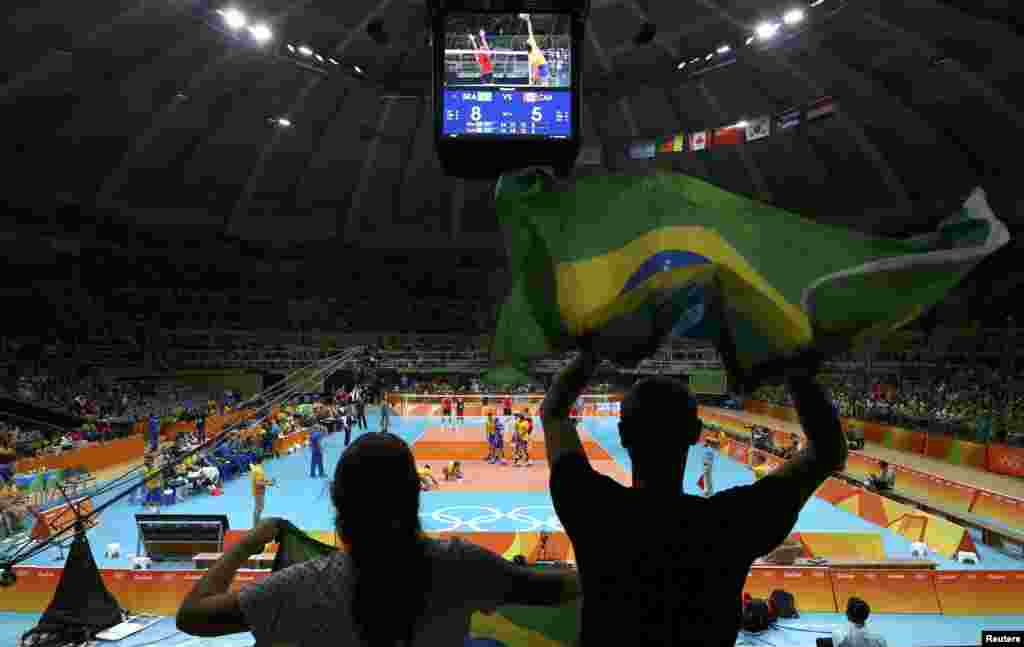Supporters hold Brazilian flags during their country's volleyball game against Canada.