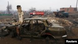 Последствия пожара в одном из населенных пунктов Хакасии — разрушенный пожаром дом и сгоревший автомобиль.