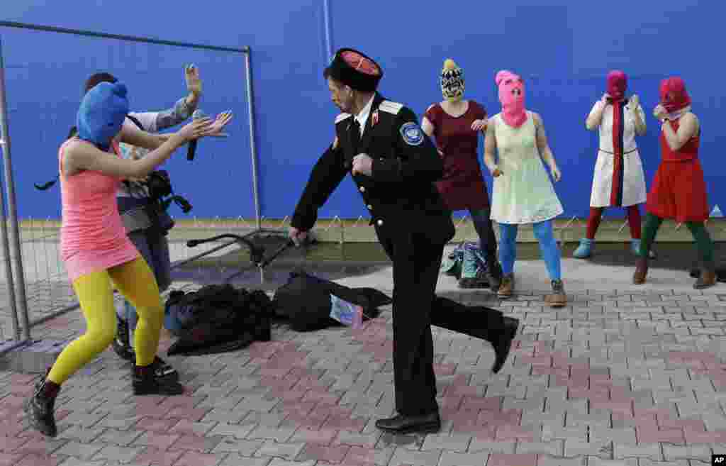 A Cossack attacks Nadezhda Tolokonnikova and a photographer as she and fellow members of the punk group Pussy Riot stage a protest performance in Sochi.