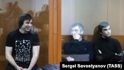 Left to right: Mokhmad Mezhidov, Elman Ashayev, and Aslan Baisultanov inside a glass-walled cage during a court hearing in Moscow late last year/