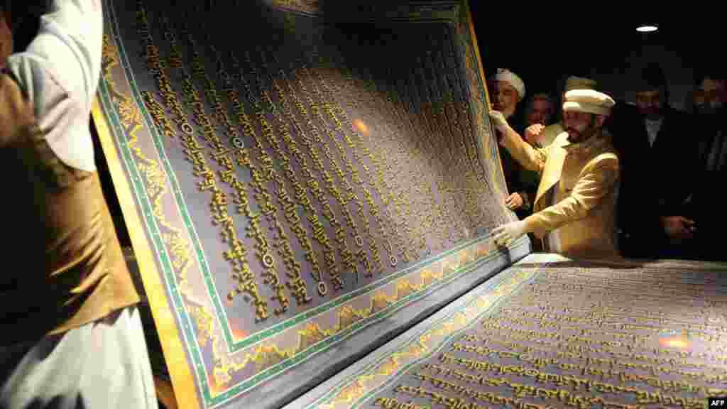 Un artist afgan și discipolii săi expun o pagină uriașă din Coran la inaugurarea Bibliotecii Naser Husro Balhi din Kabul pe 12 ianuarie. (AFP/Șan Marai)