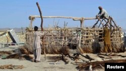 Survivors of the September 24 earthquake use poles to build a makeshift shelter near the rubble of a mud house after it collapsed in the Awaran district of Balochistan Province.