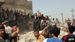 Onlookers and rescue teams gather at the scene of a bomb blast in Baghdad today.