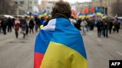 Учасник акції, яка пройшла за день до «референдуму» в Криму (визнаного більшістю країн світу незаконним), стоїть з прапорами України і Росії. Москва, 15 березня 2014 року