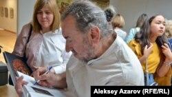 Вячеслав Люй-Ко оставляет автограф в иллюстрированном альбоме своих работ, изданном к открытию выставки. Алматы, 25 мая 2018 года.