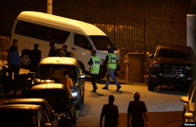 Malaziya policiyası eks-prem'er Najib Razaktıñ üyiniñ aldında. Kuala-Lumpur, 16 mamır 2018 jıl.