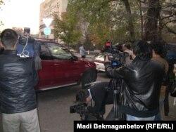 Журналисты снимают на фото- и видеокамеру отъезжающую от здания Национального пресс-клуба машину топ-бизнесмена Маргулана Сейсембаева. Алматы, 11 ноября 2010 года.