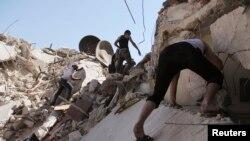 تصاویری که در حلب پس از «حمله موشکی ارتش سوریه» منتشر شده، شهروندان را در اطراف یکی از ساختمانهای فرو ریخته نشان میدهد