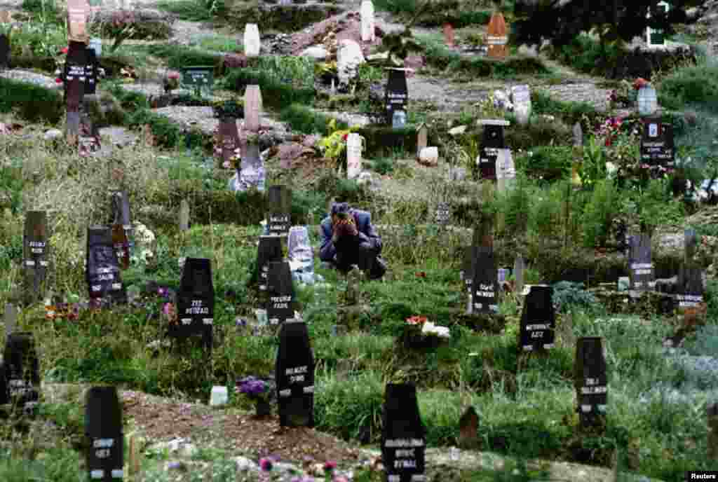 A man mourns his wife in one of Sarajevo's ever-expanding cemeteries in 1993.