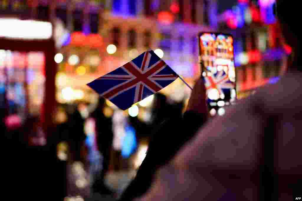 Bir qadın Belçika-Büyük Britaniya arasındaki dostluq tedbiri vaqtında cep telefonı ile Büyük Britaniya bayrağını çeke, 2020 senesi yanvarniñ 30 Belçikada Gran-Plas. Yanvarniñ 31-nde Büyük Britaniya AB terkibinden çıqtı.