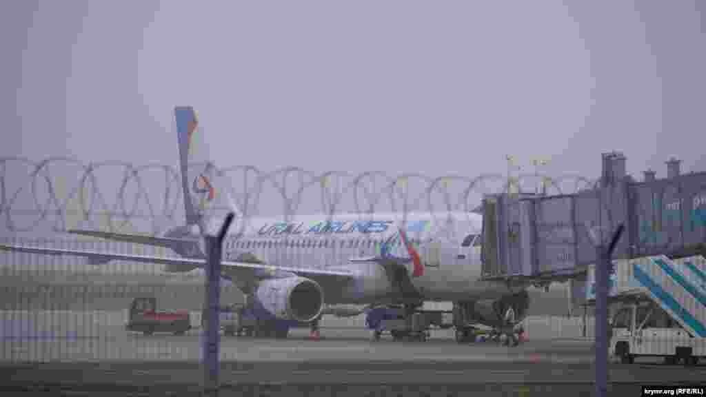 Работники аэропорта разгружают самолет «Уральских авиалиний»