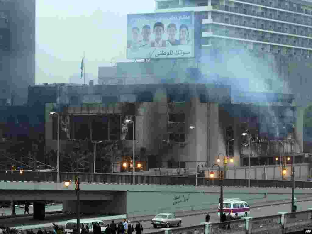 Smoke rises from the burned-out headquarters of the ruling National Democratic Party (NDP) in Cairo on January 29.