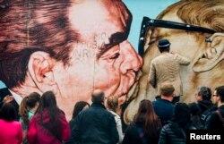 """Композиция Дмитрия Врубеля """"Братский поцелуй"""", запечатлевшая Брежнева и Хонеккера, – один из самых известных образов, связанных с падением режима ГДР"""