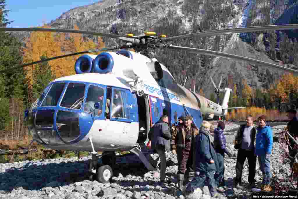 Visitors, including filmmakers planning a documentary, arrive by helicopter on a rocky bank of the Abakan River near the home of Agafia Lykova.