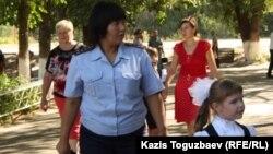 Бірінші сынып оқушысы мен мектеп жанындағы полиция инспекторы. Алматы, 1 қыркүйек 2014 жыл. (Көрнекі сурет.)