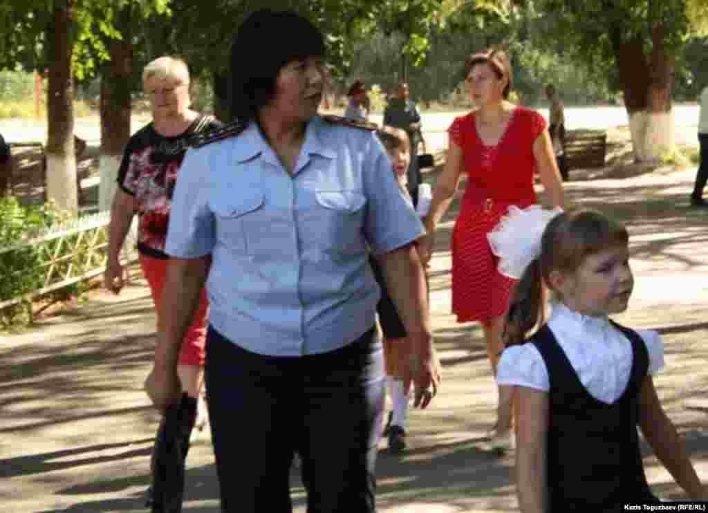 Школьный инспектор с первоклассницей, ненадолго потерявшей в суматохе своих родителей на празднике первого звонка в школе-гимназии № 60 в Алматы. 1 сентября 2014 года.