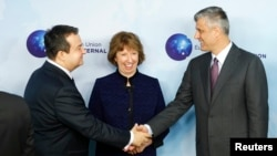 Serbian Prime Minister Ivica Dacic (left) shakes hands with Kosovo's Prime Minister Hashim Thaci during a joint meeting with European Union foreign-policy chief Catherine Ashton in Brussels on December 13.