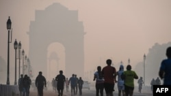 Indian joggers exercise on a smoggy morning near the India Gate monument in New Delhi.
