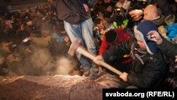 Группа протестующих разрушает памятник Ленину.