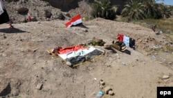العلم العراقي يغطي ما يعتقد أنها مقبرة جماعية لضحايا سبايكر قرب تكريت - 7 نيسان 2015
