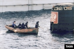 A group of workers approach the conning tower of the Kursk submarine, which was raised from the seafloor in 2001.