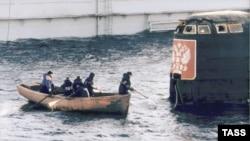 """Рабочие дока ПД-50 приближаются к боевой рубке подводной лодки """"Курск""""."""