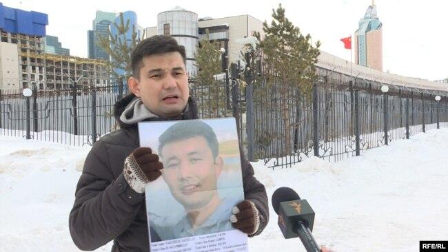 Байболат Кунболатулы с портретом брата Баймурата у здания посольства Китая в Нур-Султане. 20 февраля 2020 года.