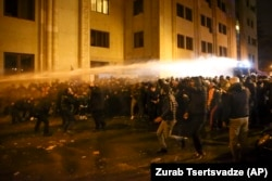 Police use a water cannon against demonstrators as they try to block the entrances to parliament in Tbilisi on November 26.