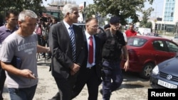 Police escort former Kosovo Central Bank Governor Hashim Rexhepi (second left) after his arrest in Pristina last year.
