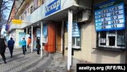 Обменный пункт и магазины на первом этаже жилого дома в Шымкенте. 17 февраля 2014 года.