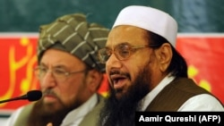 FILE: Hafiz Saeed (R), the founder of Lashkar-e-Taiba, talks journalists in Rawalpindi in 2012.