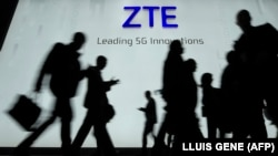 People walk in front of the ZTE stand at the Mobile World Congress (MWC), the world's biggest mobile fair, on February 27, 2018 in Barcelona.