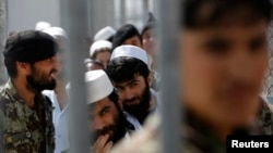 Prisoners stand in line for release during a ceremony handing over the Bagram prison to Afghan authorities at the U.S. air base north of Kabul in March 2013.