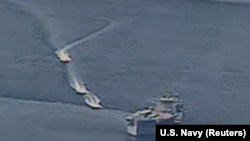 Three Revolutionary Guards vessels maneuver near a U.S. Navy ship in the Persian Gulf in April.
