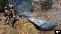 Pakistani soldiers stand next to what Pakistan says is the wreckage of an Indian fighter jet shot down in Pakistan-controlled Kashmir in the Somani area of Bhimbar district near the Line of Control on February 27.