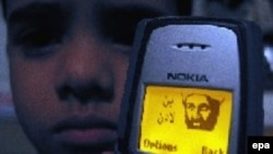 Still a fan? A young Pakistani boy with an image of Al-Qaeda leader Osama bin Laden on his mobile phone in Karachi in 2003.