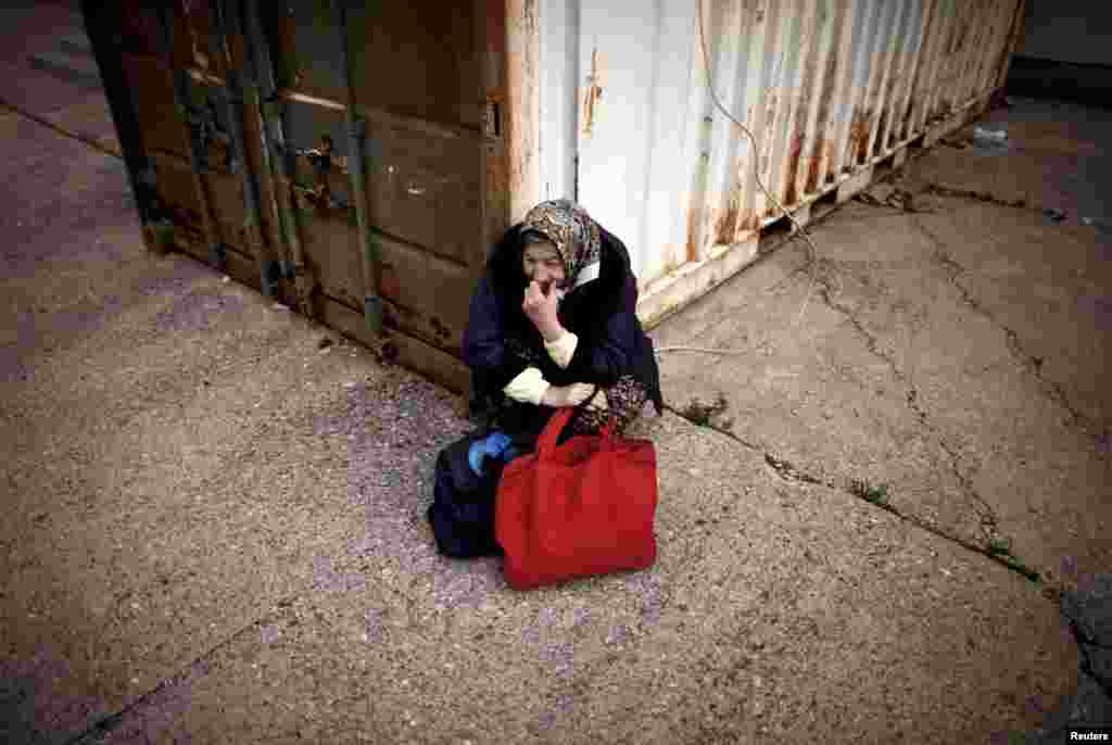 A woman waits for food in front of a soup kitchen. Some 600 residents depend on the public kitchens for their daily meals.