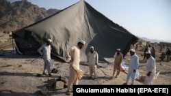 People survey the scene of a suicide bomb attack in Mohmand Dara district of Nangarhar Province on September 11.
