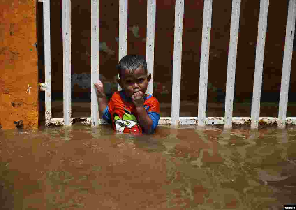 A child holds on to a fence at his house during a flood at the Kampung Melayu residential area in Jakarta on December 23. (Reuters/Beawiharta)