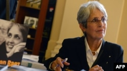 U.S. folk singer Joan Baez signs her autobiography during a visit to Prague on September 16.