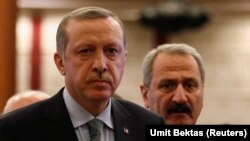 Recep Tayyip Erdogan (L) arrives for a news conference as he is flanked by former Economy Minister Zafer Caglayan. File photo 2013