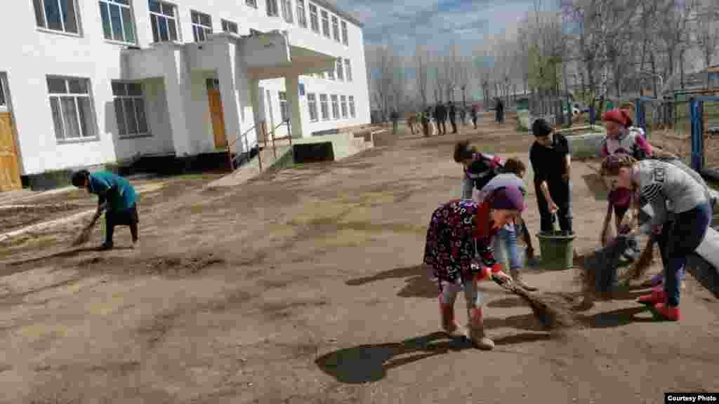 Дети подметают двор своей школы.